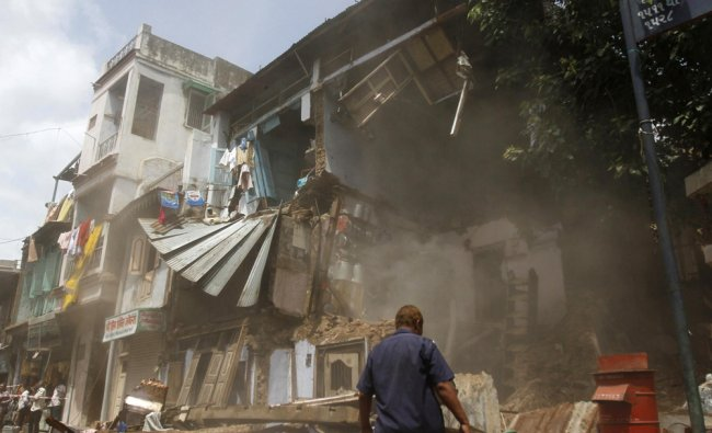 A member from the Ahmedabad Fire and Emergency Services walks amidst the rubble...