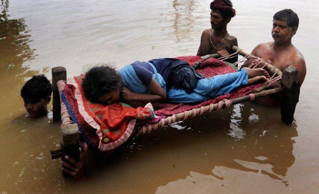 People carry a patient on a cot at flood-hit Masandpur village