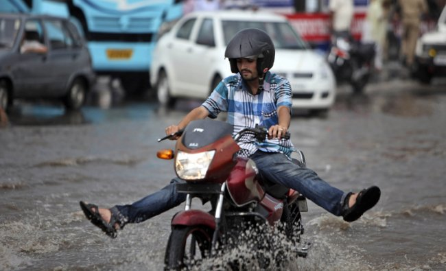 A man holds his legs up to prevent them from getting wet