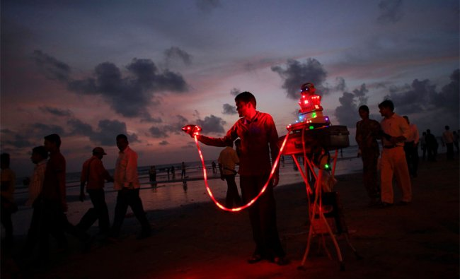 Shyaam, 28, holds a headset to a fortune telling machine as he calls out to customers at Juhu Beach