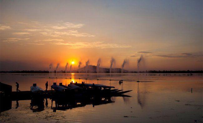 The sun sets over the Dal Lake as Kashmiri Shikara, traditional boats, owners wait for customers...