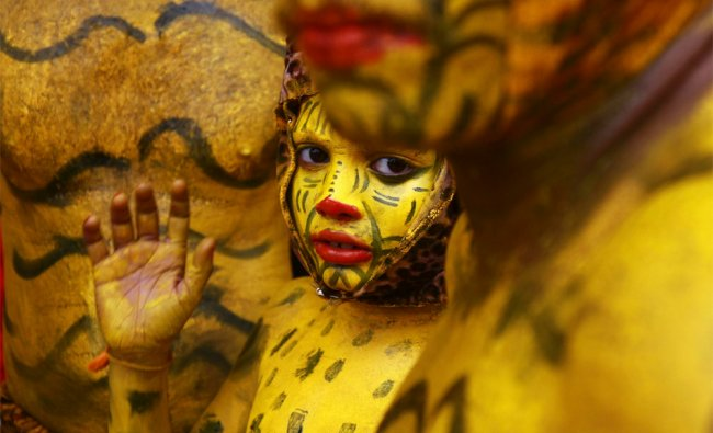 A boy with his body painted like a tiger waits backstage before performing during festivities...