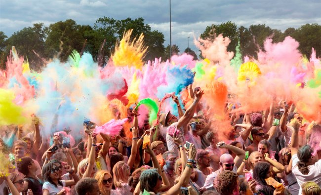 People throw colored powder into the air during the Holi Festival in Dresden Germany....