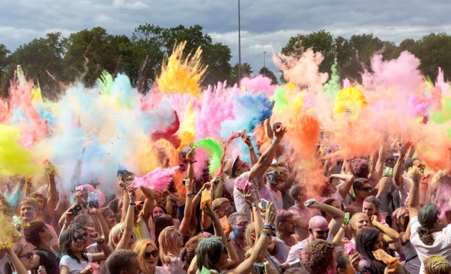 People throw colored powder into the air during the Holi Festival in Dresden Germany...