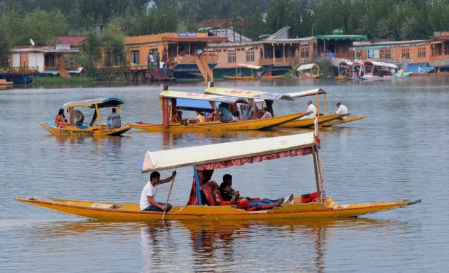 Tourists enjoy a trip aboard the typical Shikara boats on the World Famous Dal Lake...