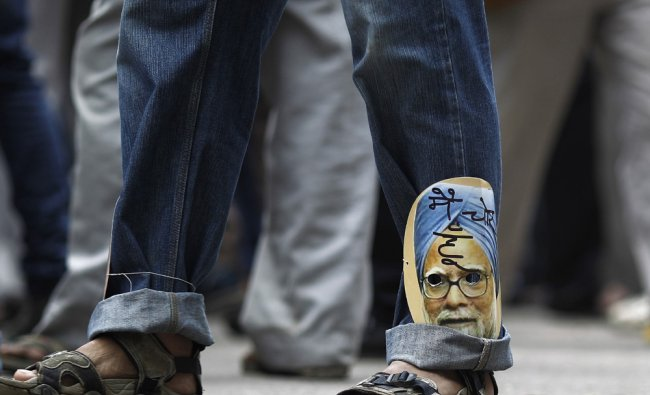A supporter of veteran Indian social activist Anna Hazare wears a cut-out ...