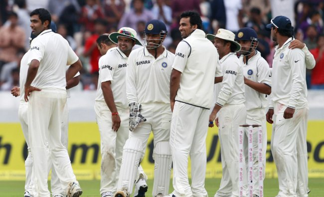 Ravichandran Ashwin watches replay on the screen with his teammates after the dismissal of James...