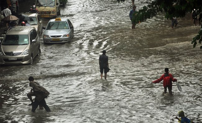 Indian pedestrians walk through a flooded street during heavy rains in Mumbai