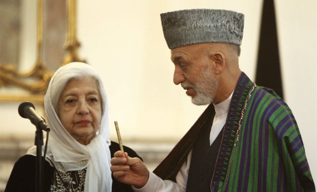 Princess India watches as Hamid Karzai (R) holds a pen which belonged to her father