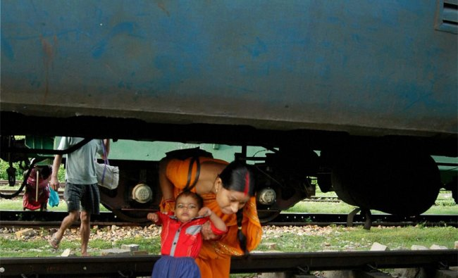 A woman crosses a stationary train at a railway station in Allahabad