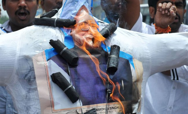 Members of the BJP shout slogans as they burn an effigy of Manmohan Singh