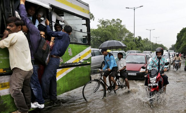 People commute through a flooded street after heavy monsoon rains in New Delhi