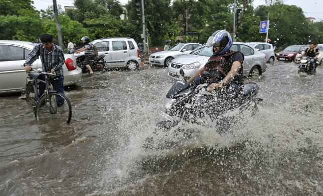 A man rides his motorbike through a flooded street after heavy monsoon rains in New Delhi