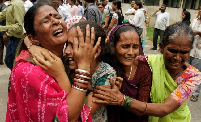 Relatives of an accused cry after hearing a court verdict in a 2002 religious violence case, in Ahm