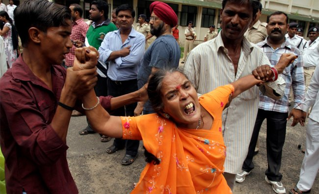 Relative of an accused reacts after hearing a court verdict in a 2002 religious violence case, in Ah