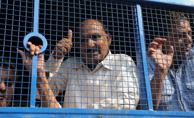 Bajrang Dal leader Babu Bajrangi gestures from the window of a police vehicle in Ahmedabad...