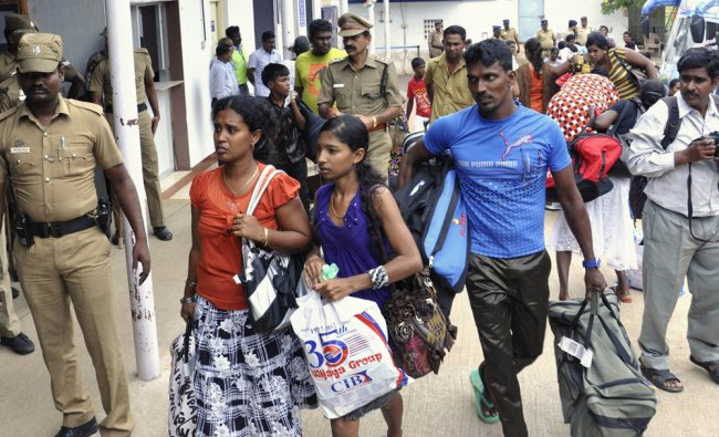 Policemen escort Sri Lankan pilgrims after they were mobbed by locals...