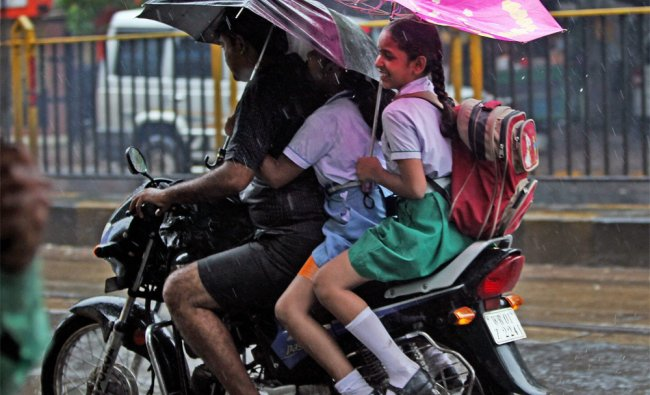 School children shield themselves from rain on their way to school in Kolkata