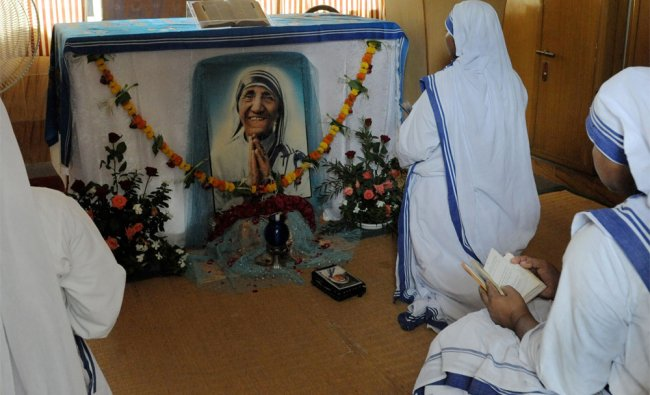 Christian nuns pray in front of a photograph of Mother Teresa on her death anniversary...