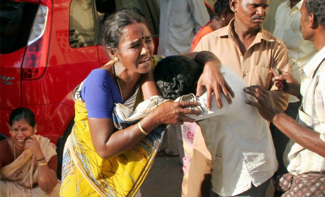 Relatives of victims of Sivakasi cracker factory cry outside the Government hospital in Madurai ...
