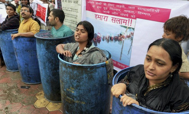 Social activists standing in water drums in Bhopal...