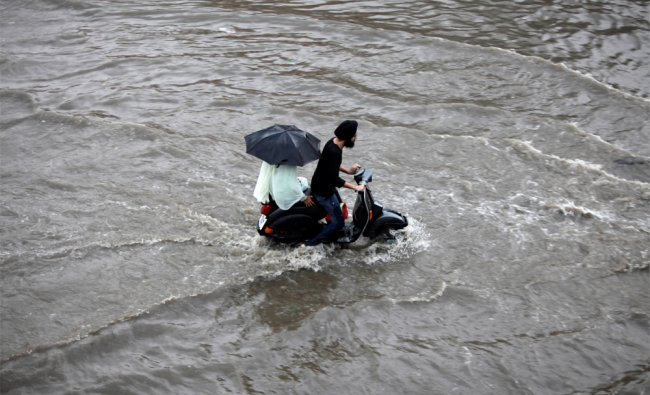 A man rides a scooter through a water logged street during monsoon rains in Jammu...