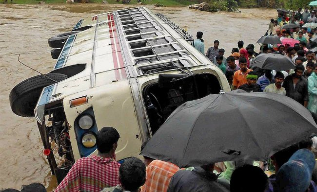 People gather to take a look at thebus that was swept away by the flooded Bhairab Baki river...