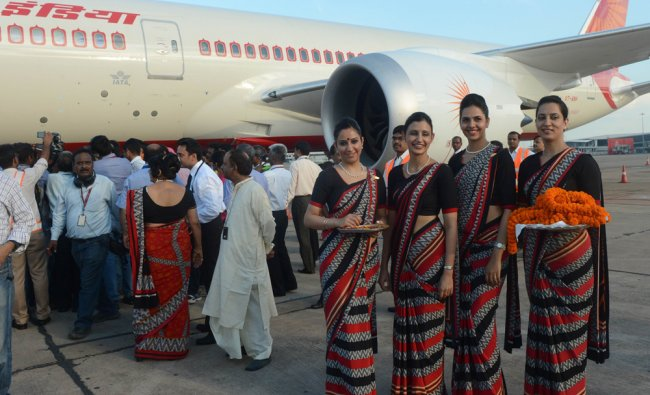 Indian Air air hostesses hold marigold flowers to welcome Air India\'s first Boeing 787 Dreamliner