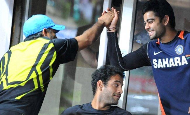 Mahender Singh Dhoni gestures with Virat Kohli
