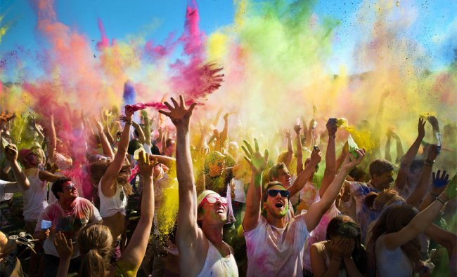 Visitors throw colour pigments in the air to celebrate the Holi Open Air at the Gallop Race Course..