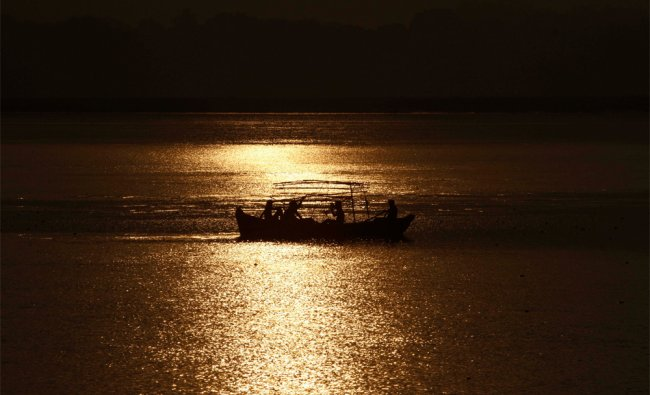 Pilgrims and tourists take a boat ride in the Ganges River, in Allahabad, India...