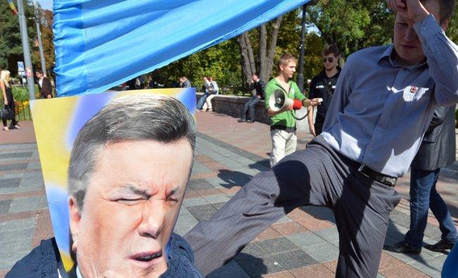 People kick a dummy symbolizing Ukrainian President Viktor Yanukovich