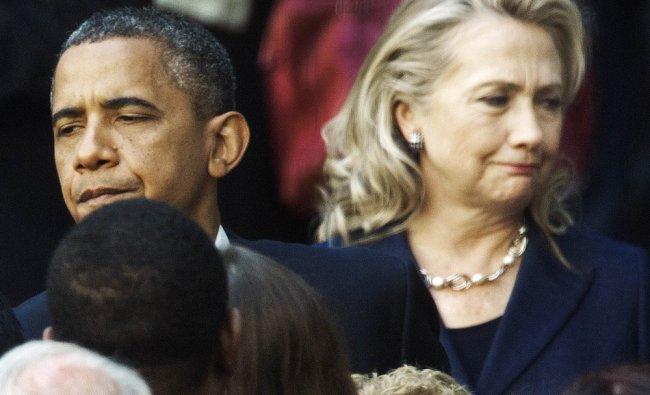 Barack Obama and US Secretary of State Hillary Clinton speak to staff members