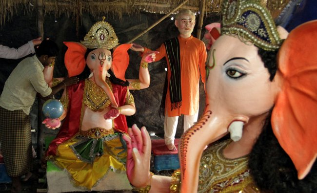 An Indian artisan makes the finishing touches to a clay idol of elephant-headed Hindu God Ganesha