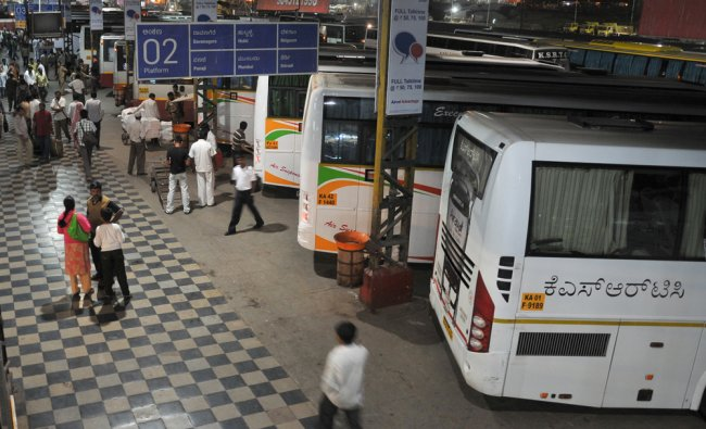 People wait for the departure of buses at the Kempe Gowda bus stand