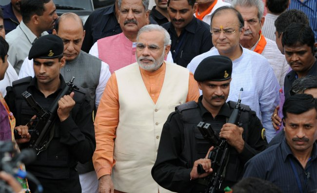 Armed commandos secure Gujarat state Chief Minister Narendra Modi (C), accompanied by former Bharati