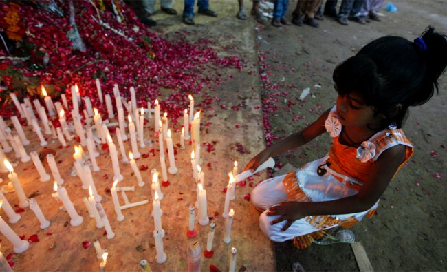 A girl lights a candle during a candlelight vigil, organized by the supporters of the political...