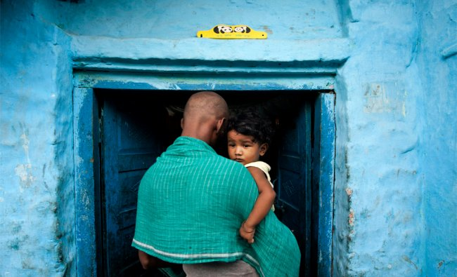 An Indian man carries a child while standing in a shanty neighborhood in New Delhi...