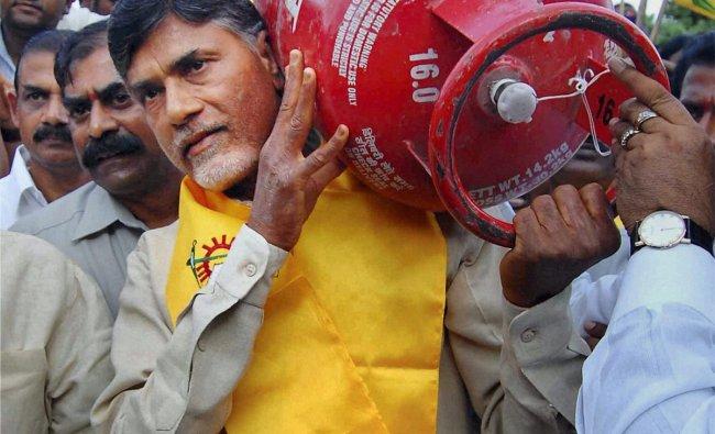 Telugu Desam Party president N. Chandrababu Naidu carries an LPG cylinder during a protest
