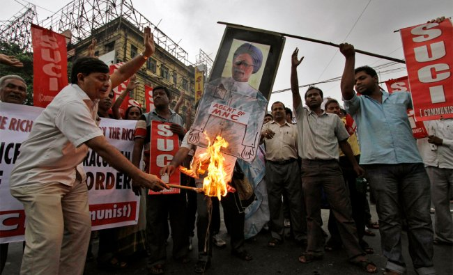 Activists of Socialist Unity Center of India (SUCI) burn an effigy with a portrait Manmohan Singh