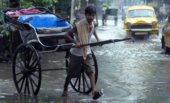 A rickshaw puller wades through a water logged street