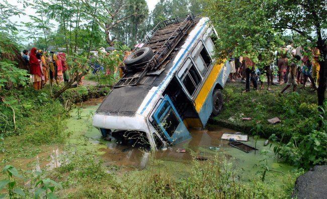 People looking at the ill-fated private bus which collided with a Taxi in Malda district...