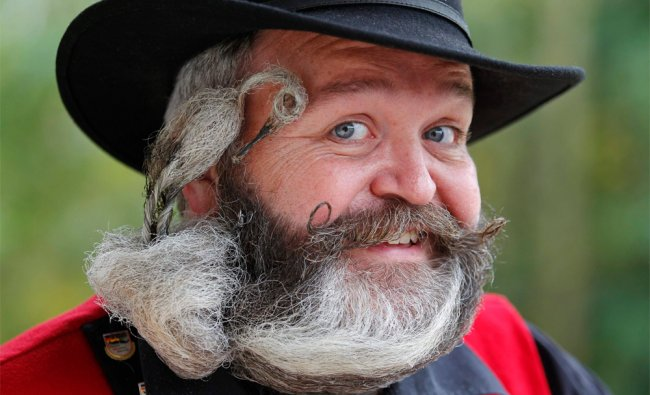 German hairdresser Elmar Weisser, 48, poses with his beard, which is shaped...