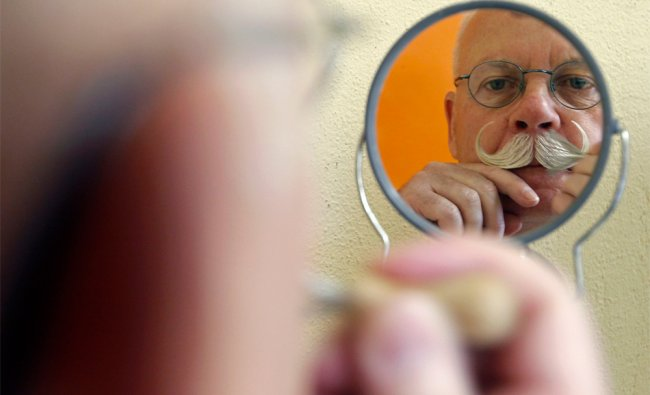 A participant is reflected on a mirror as he gets ready for the 2012 European Beard and Moustache...
