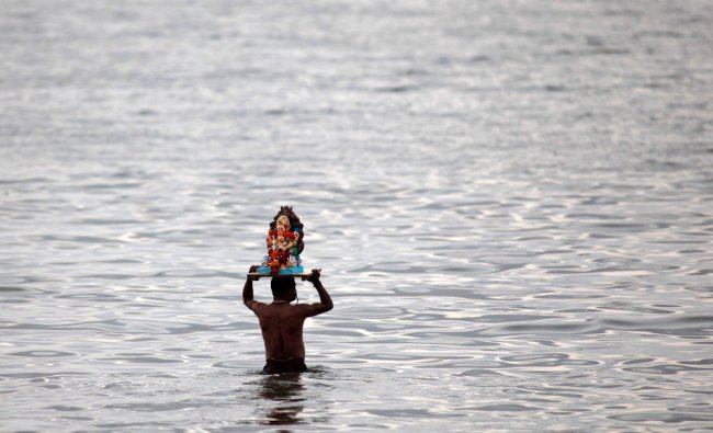A man carries an idol of the Hindu elephant headed god Ganesha to immerse it in the Arabian Sea