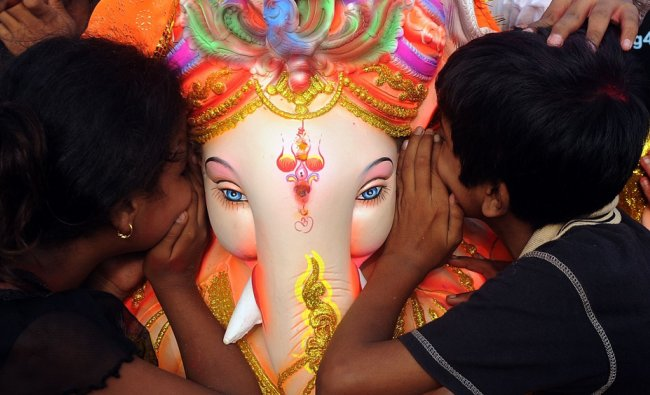 Devotees whisper their wishes into the ear of an idol of Ganesha