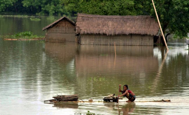 Flood affected women row to safer area on a makeshift banana raft in flooded Kuthori village
