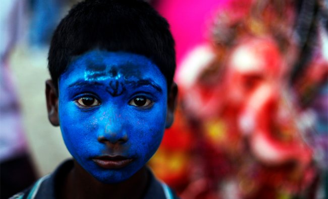 A boy with his face painted blue like the Hindu god Shiva, stands near an idol of elephant...