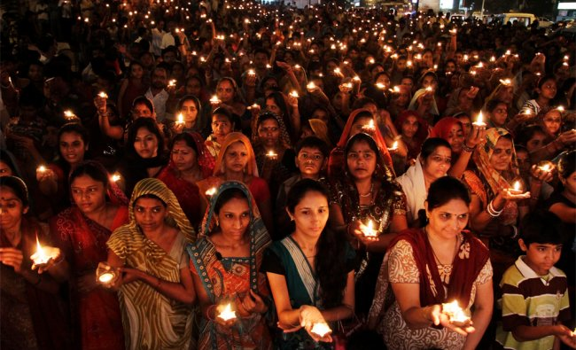 In this photo taken Sunday, Sept. 23, 2012, Indian Hindu women and children hold earthen lamps...