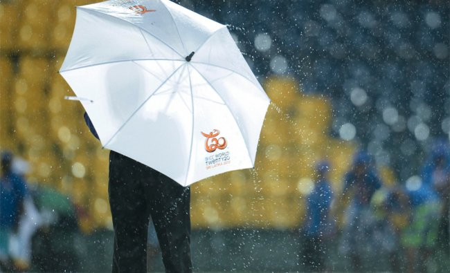 Umpire Aleem Dar stands in the rain during a delay in the match between Ireland and West Indies...